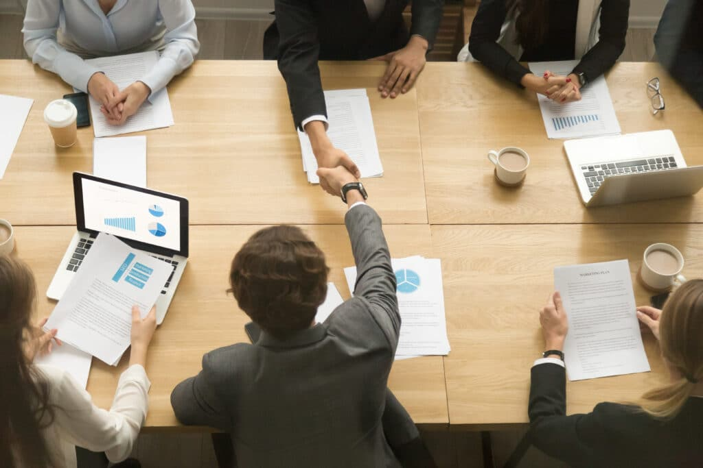 Businessmen,Shaking,Hands,Sitting,At,Conference,Table,During,Team,Meeting,